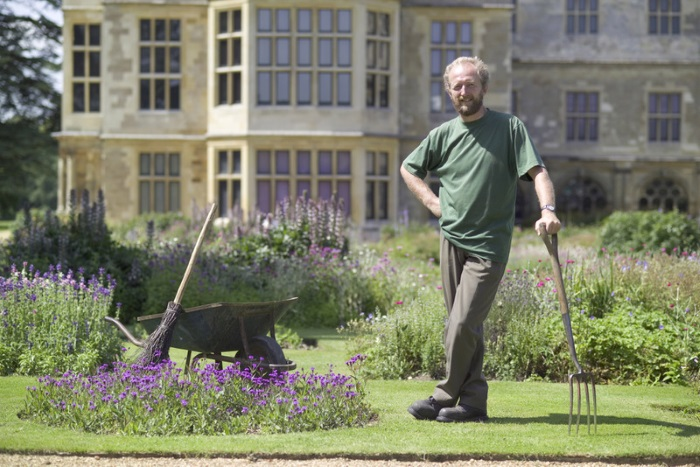 Audley End is an early 17th century country mansion, which was once a palace in all but name. A gardener rests on his fork in front of the house., Audley End, Essex, England.