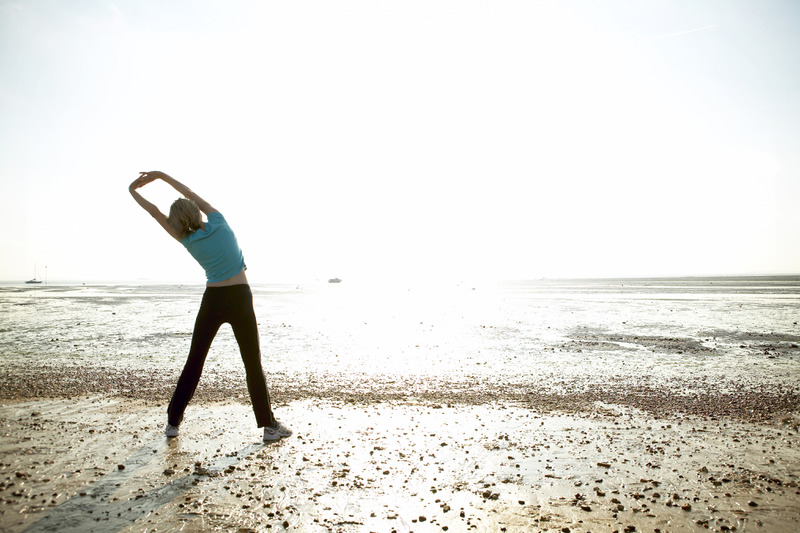 A woman exercising on the beach at low tide at Shoebury., Shoebury, Essex, England. Additional Credit: Southend-on-Sea Bor. Council