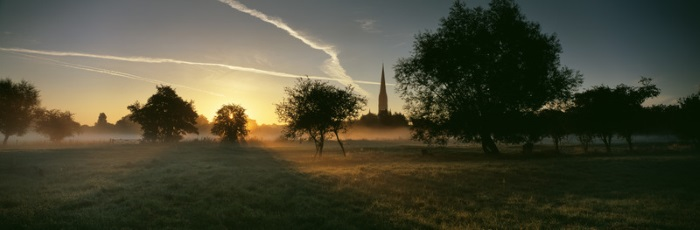 Salisbury Cathedral at dawn rising above the mist lying on Harnham Water Meadows., Salisbury, Wiltshire, England.