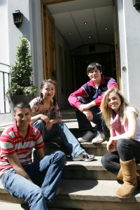 Group of young people sitting on the steps outside the Abbey Road recording studios, made famous by The Beatles in the 1960s, St Johns Wood, London, London, England.