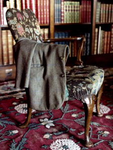 A Jacket lying over the arm of a chair in the Long Library of Eastnor Castle. Originally created in Gothic style, the Long Library was redesigned for the 3rd Earl by the decorator, Fox, in Renaissance style. The library contains some 5, 000 books, many of which came from the collection of the eminent historian, Dr Treadway Nash, whose daughter married the 1st Earl., Eastnor Castle, Herefordshire, England.