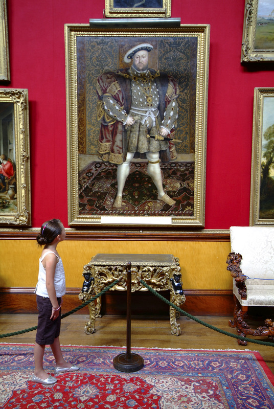 A young girl looks up inquisitively at a painting of Henry VIII by Holbein, which stands proudly in the Picture Gallery of Belvoir Castle. Built in the late 17th century, Belvoir Castle stands dramatically, on a Leicestershire hilltop, dominating the surrounding countryside., Belvoir Castle, Leicestershire, England. Additional Credit: East Midlands Tourism