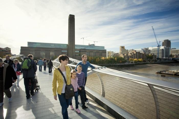 Family walking across Millennium bridge with Tate Modern in background, London, England, UK.