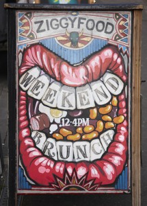 Hoxton in East London. A cafe sign, Ziggy's Food. A huge mouth advertising weekend brunch. Street art.