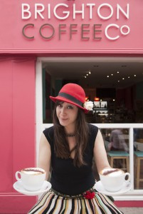 The Brighton Coffee co, a coffee shop with a pink front and large sign. A cafe in Brighton. A young woman in a smart hat and apron. Waitress holding two full cups of coffee.