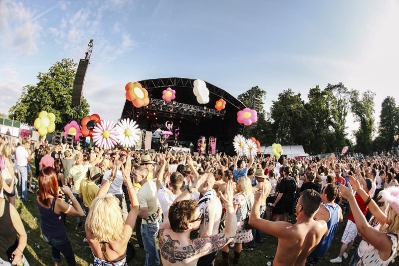A live music event, a summer music festival in Wales. A large group of people, young and old, men and women, with their hands in the air, clapping along to the band playing on stage. Decorations, balloons and cardboard flowers. Flower power.