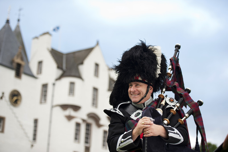 A highland piper in traditional dress, wearing a tartan kilt, jacket, sporan and busby. Playing bagpipes in front of Blair Castle, Perthshire, a castle open to the public, a fortified house.